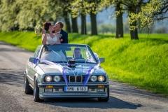 nevěsta a ženich v kabrioletu na svatbě